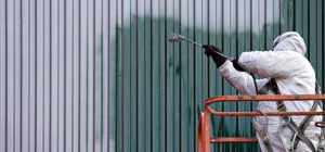 man in cherry picker airless spraying cladding in green