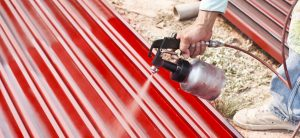 close up of man using airless spray gun in red